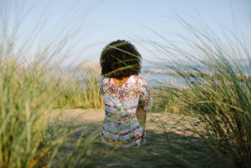 De jonge vrouw van het Afrokapsel bij het strand royalty-vrije stock fotografie