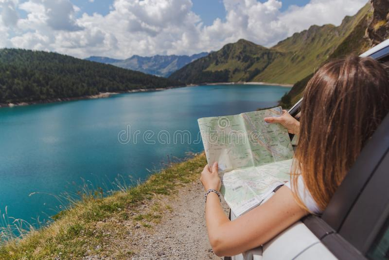 De jonge vrouw verloor in de bergen met zijn auto kijkend de kaart om de juiste weg te vinden royalty-vrije stock afbeeldingen