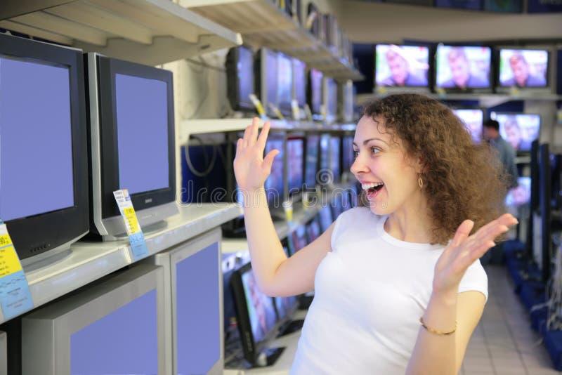 De jonge vrouw in verrukking bekijkt TVs in winkel stock fotografie