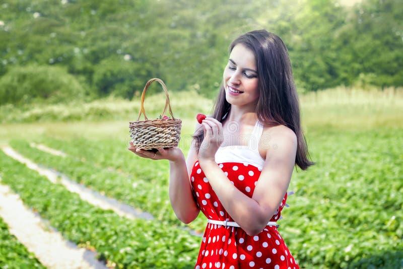 De jonge vrouw verzamelt aardbeien royalty-vrije stock foto