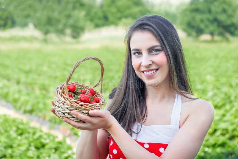 De jonge vrouw verzamelt aardbeien stock afbeelding