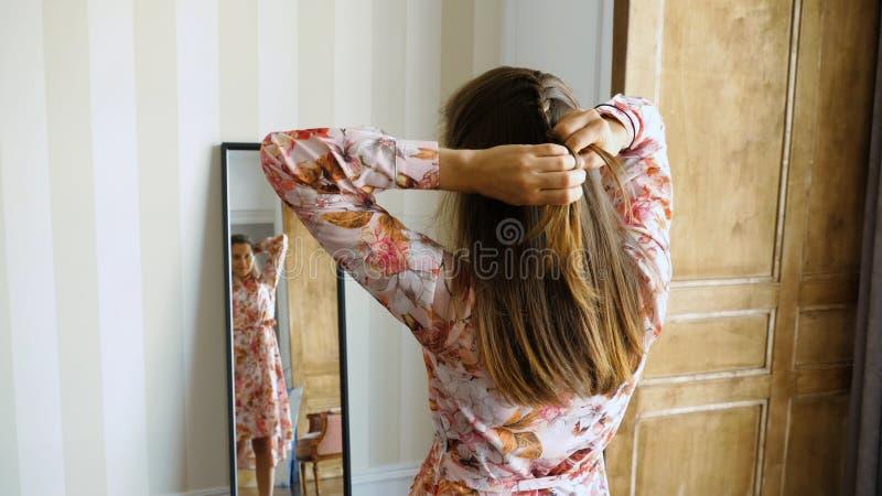 De jonge vrouw vlecht haar haar voor een spiegel stock fotografie