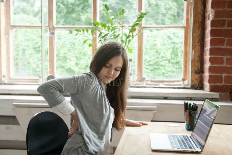 De jonge vrouw voelt ongemakkelijke zitting als bureauvoorzitter, massagi stock afbeelding