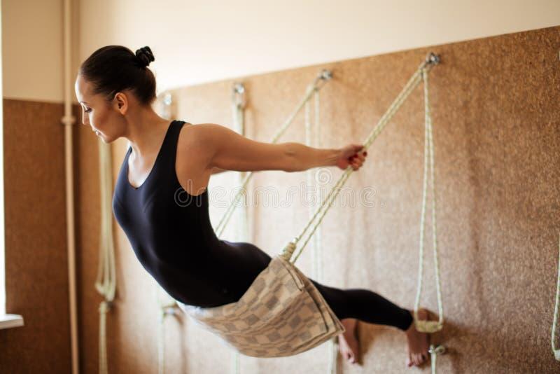 De jonge vrouw voert de yogaoefening op de kabels uit stock afbeeldingen