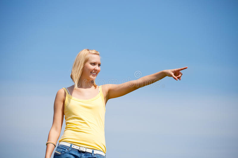 De jonge vrouw voor blauwe hemel toont richting royalty-vrije stock afbeelding