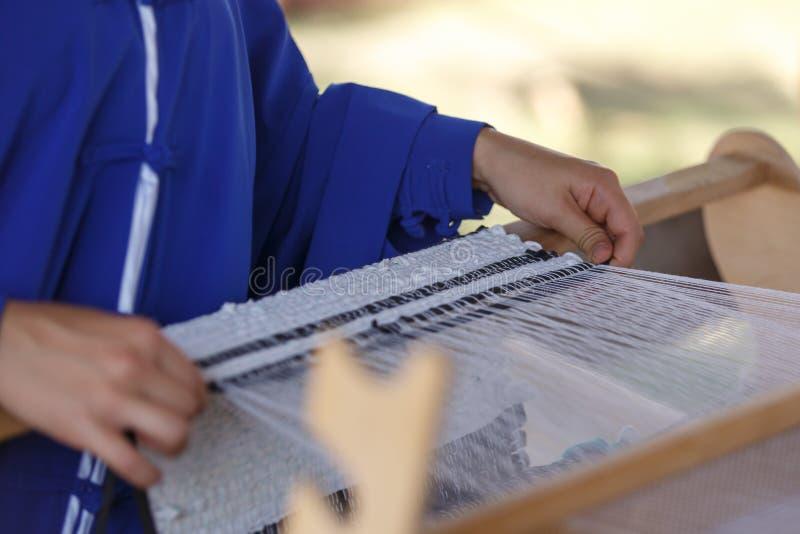 De jonge vrouw weeft een witte doek op een hand houten weefgetouw stock afbeeldingen