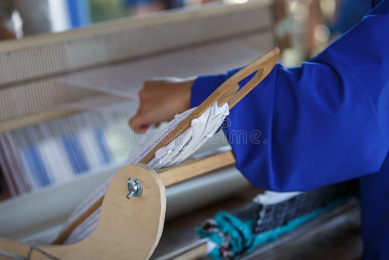 De jonge vrouw weeft een witte doek op een hand houten weefgetouw stock fotografie