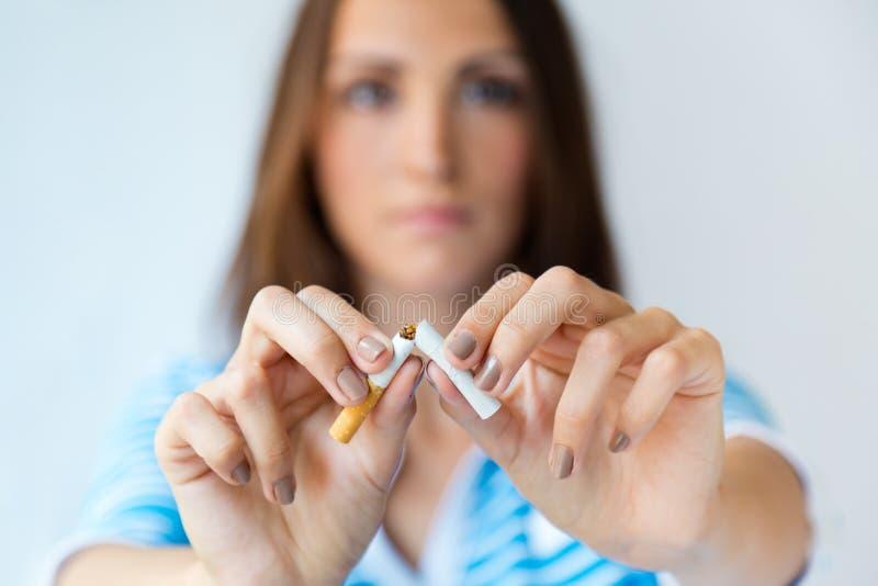 De jonge vrouw weigert te roken en breekt sigaret stock foto's