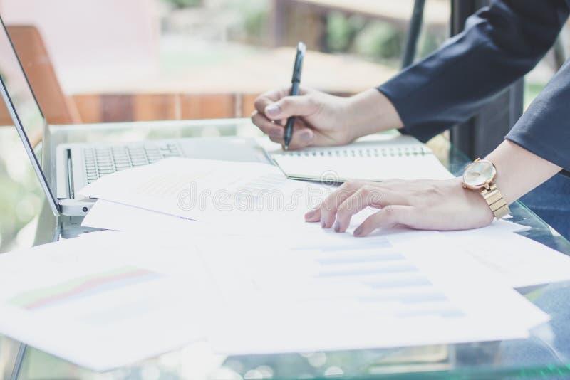 De jonge vrouw werkt in bureau, neemt de Secretaresse nota's van de telefoon, werken de Bedrijfs jonge vrouwen aan telefoons en n stock foto