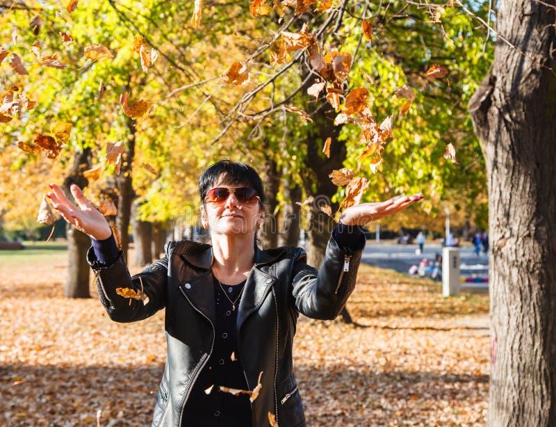 De jonge vrouw werpt op gele bladeren in het park in de herfst royalty-vrije stock foto's
