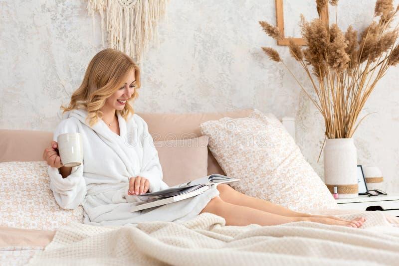 De jonge vrouw in witte badstof robe drinkt koffie en leest tijdschrift of boek in slaapkamer stock afbeeldingen