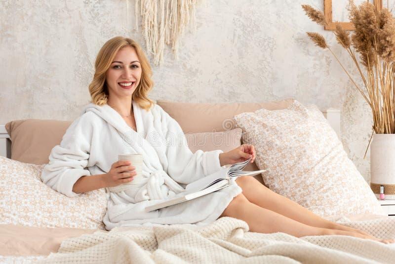 De jonge vrouw in witte badstof robe drinkt koffie en leest tijdschrift of boek in slaapkamer royalty-vrije stock foto