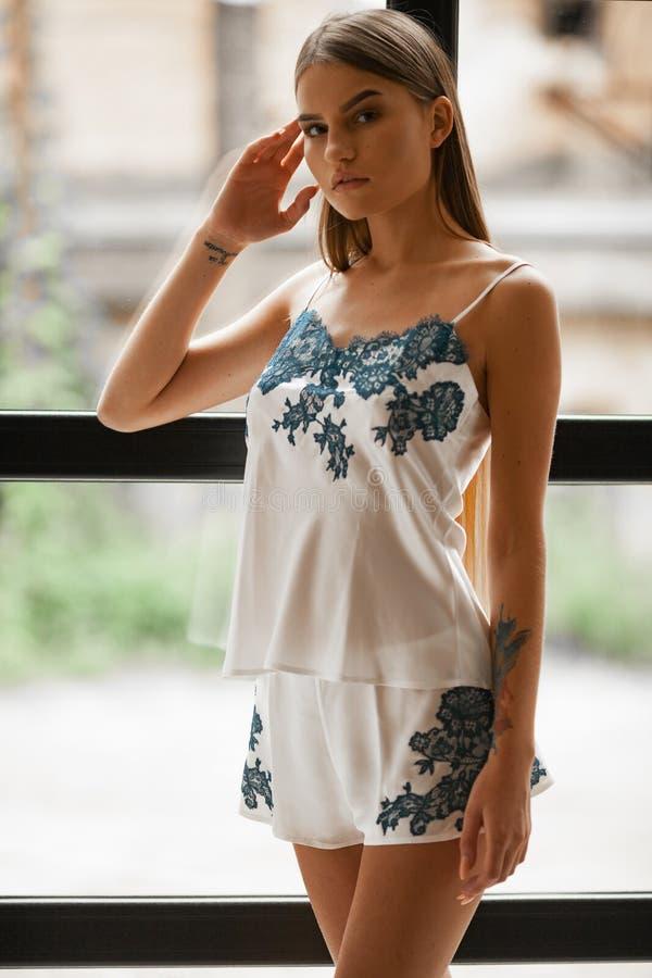 De jonge vrouw in witte pyjama's met blauwe tracery bevindt zich tegen achtergrond van venster stock foto's