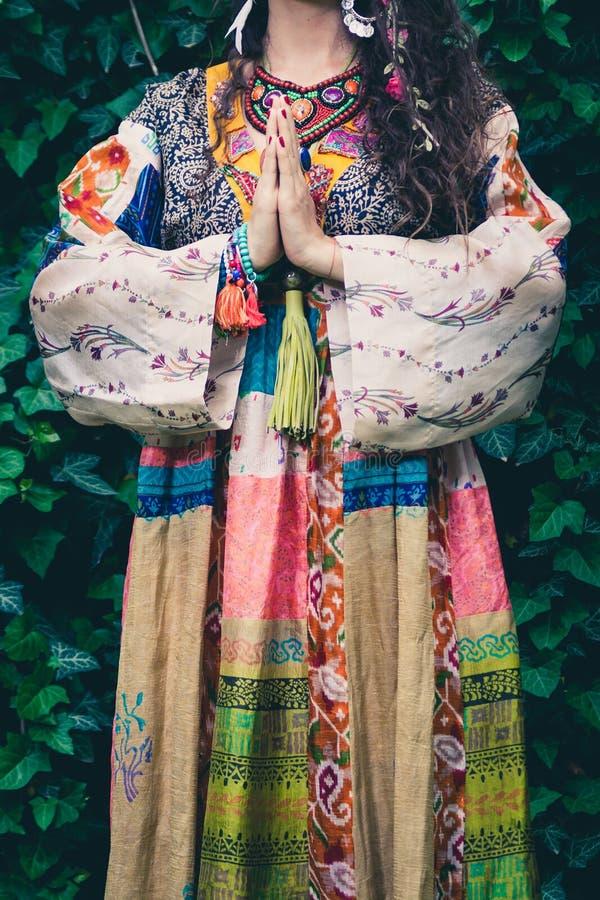 De jonge vrouw in de zijdekleding en juwelen van de bohostijl met dient de het gebaar namaste openluchtzomer in van yogamudra stock afbeelding