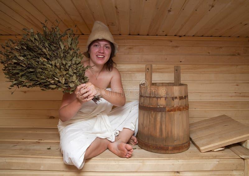 De jonge vrouw zit bij saunabad royalty-vrije stock afbeelding