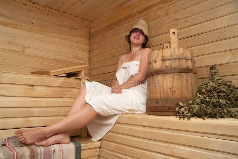 De jonge vrouw zit bij saunabad stock fotografie
