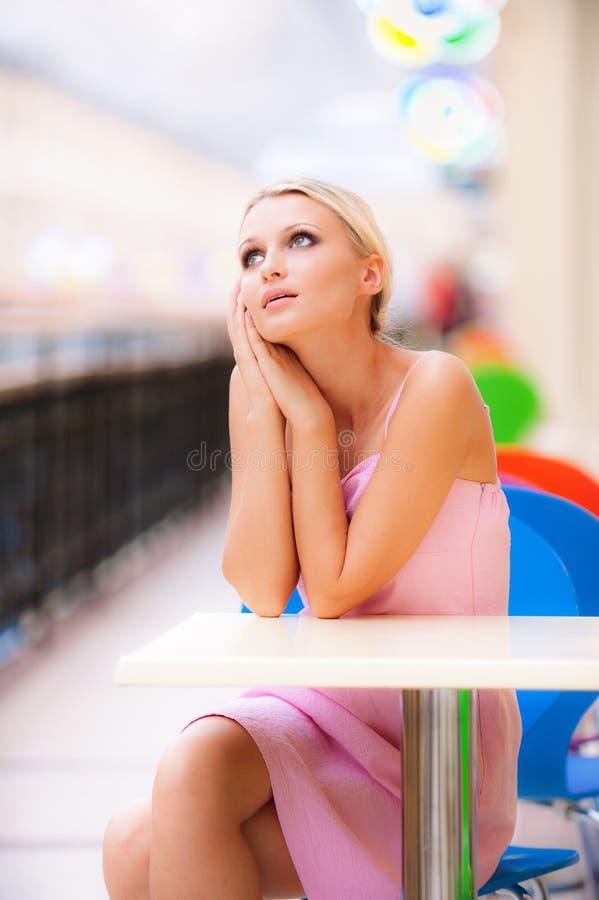 De jonge vrouw zit bij weinig lijst bij restaurant royalty-vrije stock foto's