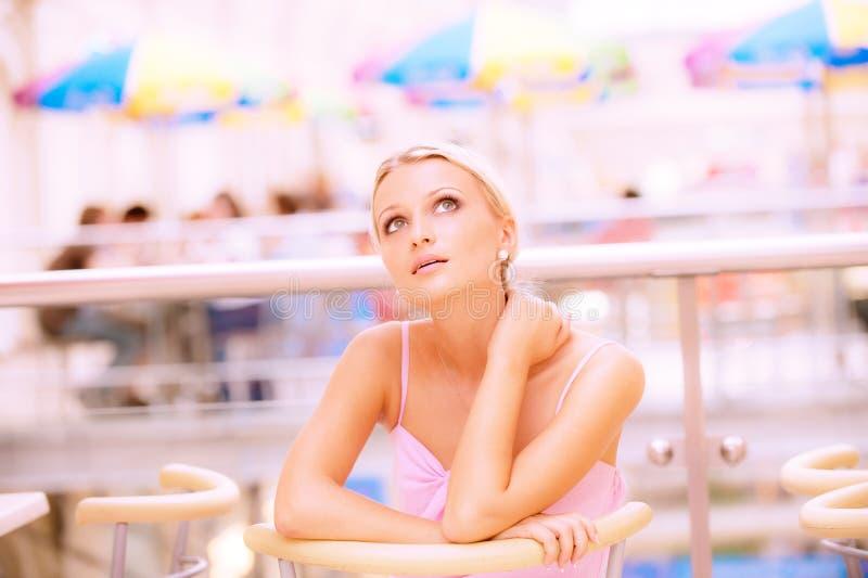 De jonge vrouw zit bij weinig lijst bij restaurant royalty-vrije stock foto