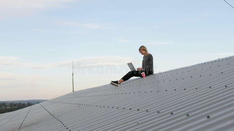 De jonge vrouw zit met laptop en het luisteren muziek op hoofdtelefoons op het dak royalty-vrije stock afbeeldingen