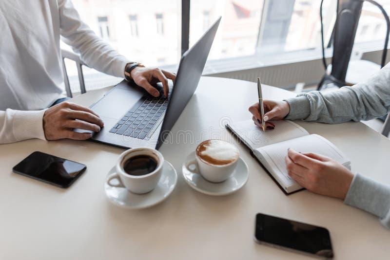 De jonge vrouw zit met werkgever en neemt nota's in een notitieboekje Twee bedrijfsmensen in een koffie op een informele vergader royalty-vrije stock afbeeldingen