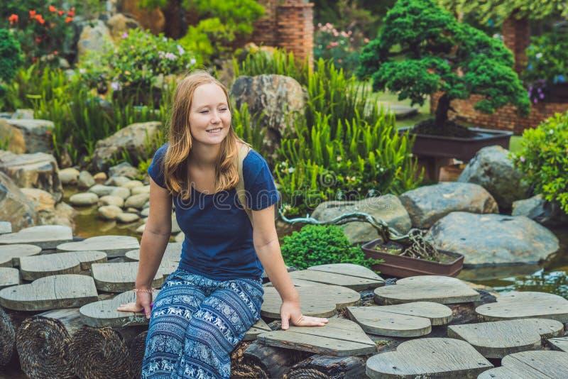 De jonge vrouw zit op de brug in het park royalty-vrije stock afbeelding