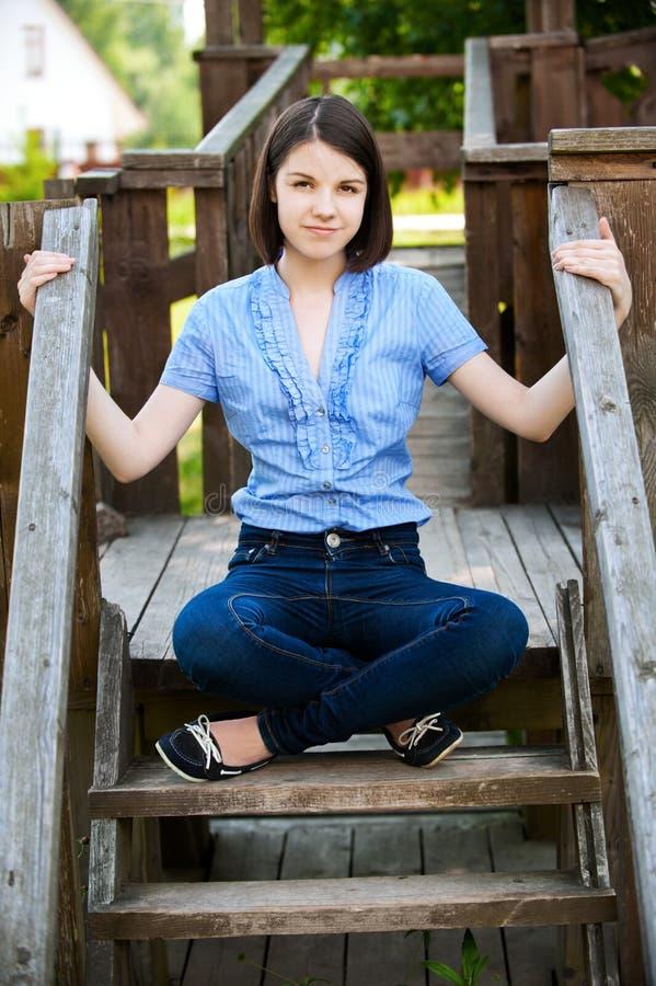 De jonge vrouw zit op houten ladder royalty-vrije stock foto's
