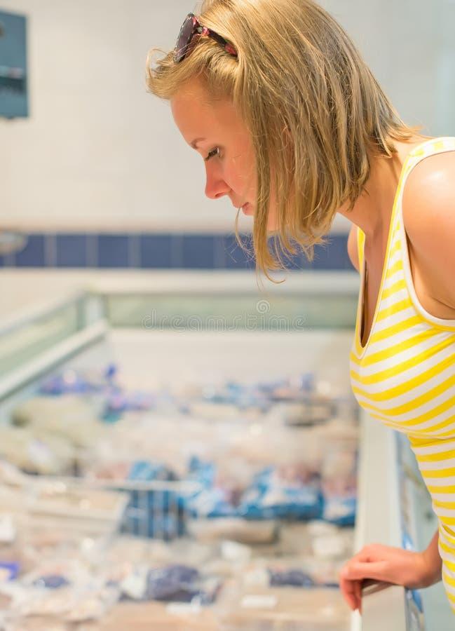 De jonge vrouw zoekt vissen stock foto