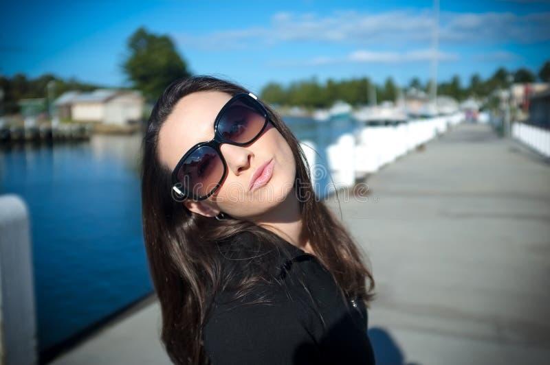 De jonge vrouw in zonnebril blaast een kus bij een werf royalty-vrije stock fotografie
