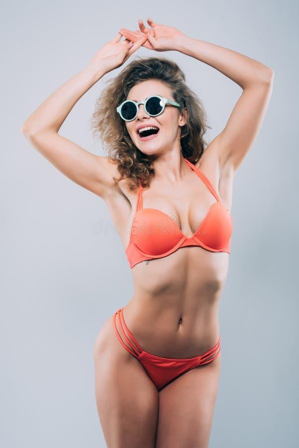 De jonge vrouw in zonnebril met mooi slank perfect lichaam in bikini isoleerde grijze achtergrond stock foto's