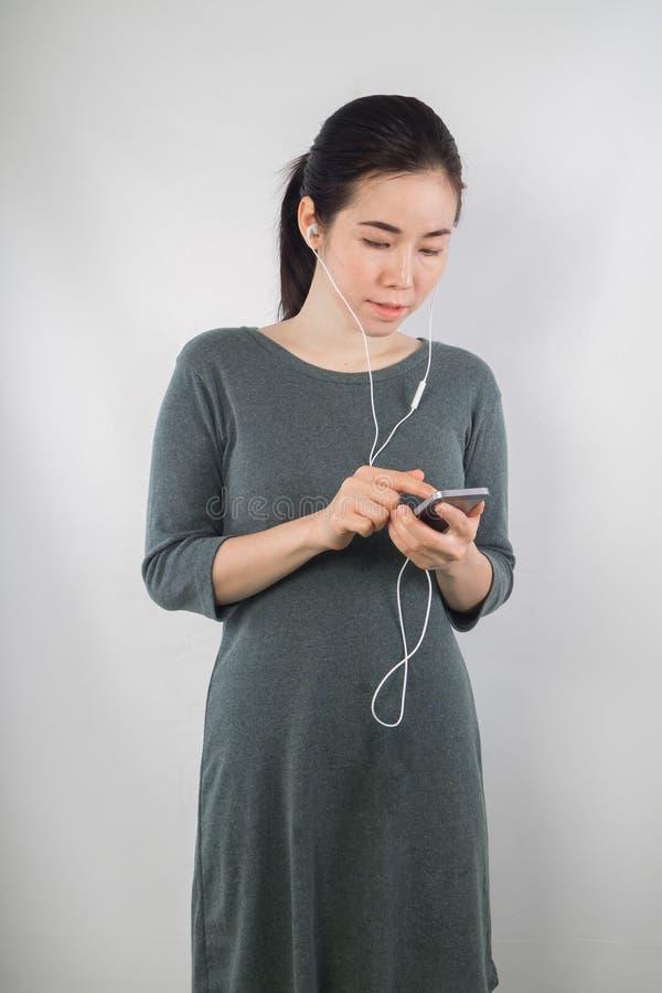 De jonge vrouw zwanger is in moederschapskleren luisterend aan muziek stock afbeeldingen
