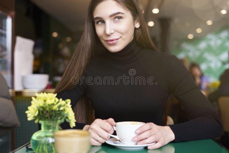De jonge vrouw in zwart Jersey kijkt aan camera, drinkt koffie en het hebben van rust in koffie dichtbij venster stock afbeelding