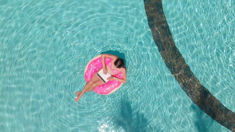 De jonge vrouw zwemt in het overzees in een zwemmende cirkel Meisje die in de pool op een opblaasbare cirkel met een computer, bo royalty-vrije stock foto