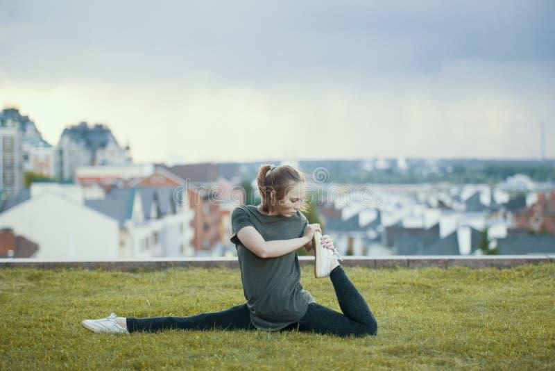 De jonge vrouwelijke acrobaat op het gras voert streng, cityscape op achtergrond uit stock afbeeldingen