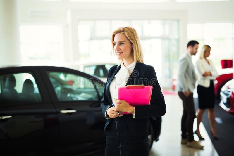 De jonge vrouwelijke adviseur die van de autoverkoop in toonzaal werken royalty-vrije stock afbeeldingen