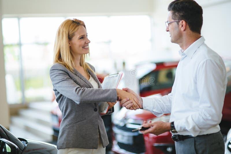 De jonge vrouwelijke adviseur die van de autoverkoop in toonzaal werken stock foto