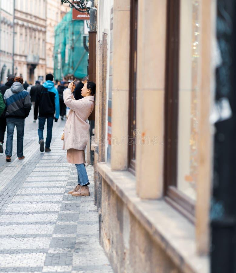 De jonge Vrouwelijke Aziatische toerist neemt foto's terwijl sightseeing in Praag, Tsjechische Republiek - Pasen-Vakantie royalty-vrije stock foto