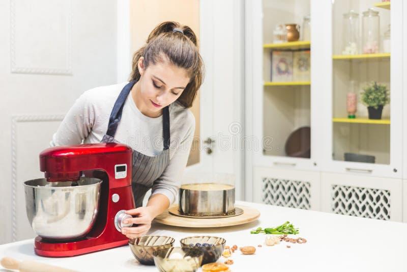 De jonge vrouwelijke banketbakker ranselt room in een metaalkom in een rode elektrische mixer Het concept eigengemaakt gebakje, h stock afbeeldingen