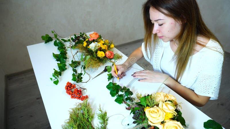 De jonge vrouwelijke bloemmanager houdt verslag van bloemen bij en schrijft o royalty-vrije stock afbeelding