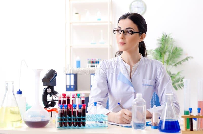 De jonge vrouwelijke chemicus die in het laboratorium werken royalty-vrije stock foto's