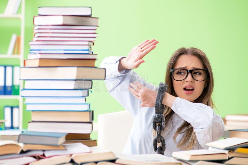 De jonge vrouwelijke die student aan het bureau en het voorbereidingen treffen voor examens met vele boeken wordt geketend stock foto's