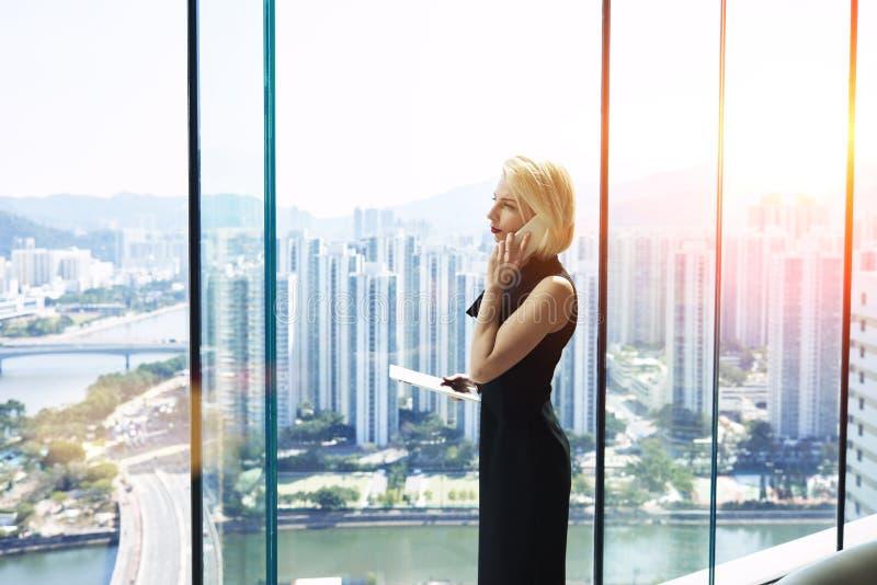 De jonge vrouwelijke econoom roept via mobiele telefoon royalty-vrije stock foto's