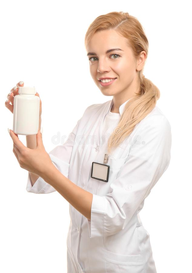 De jonge vrouwelijke fles van de apothekerholding met geneesmiddel op witte achtergrond royalty-vrije stock afbeelding