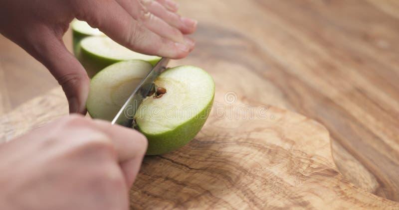 De jonge vrouwelijke handen snijden groene appel in kwarten royalty-vrije stock afbeeldingen