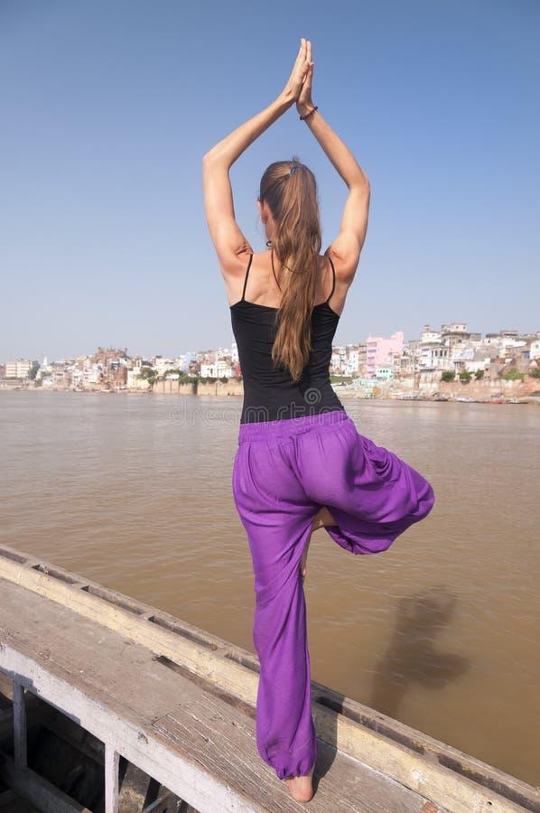 De jonge vrouwelijke het praktizeren houding Vrksasana van de yogaboom stock afbeelding