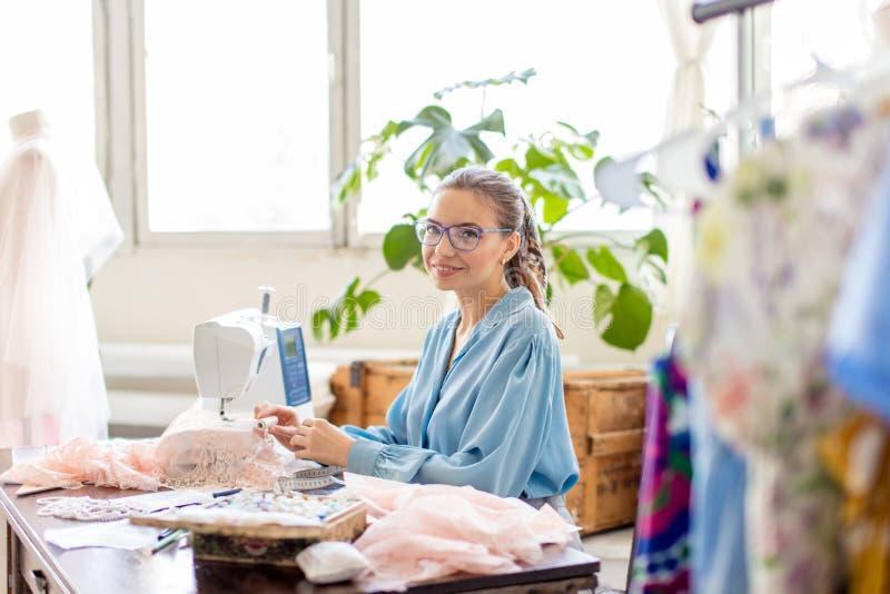 De jonge vrouwelijke kleermaker zit op het werk en kiest kleur van draden in atelier stock afbeelding