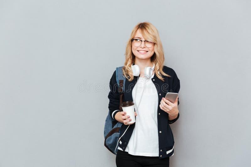 De jonge vrouwelijke kop van de studentenholding van koffie en smartphone stock afbeelding