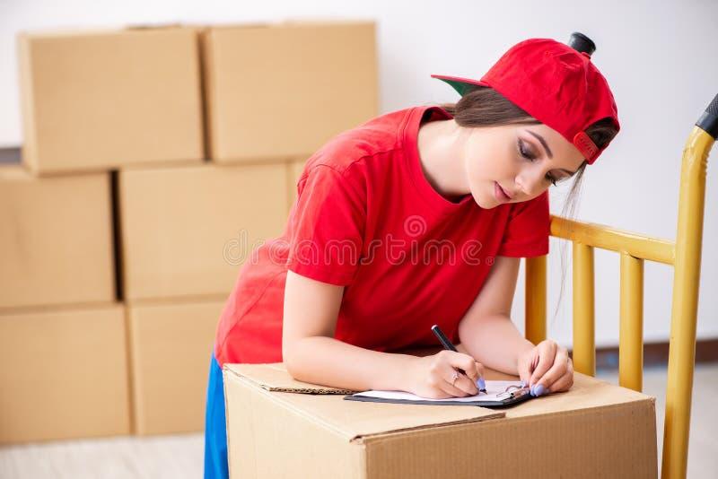De jonge vrouwelijke professionele verhuizer die huisverhuizing doen stock afbeeldingen