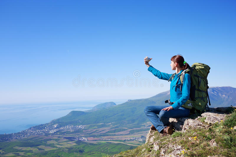 De jonge vrouwelijke reiziger met packpack bij berg lanscape maakt stock fotografie