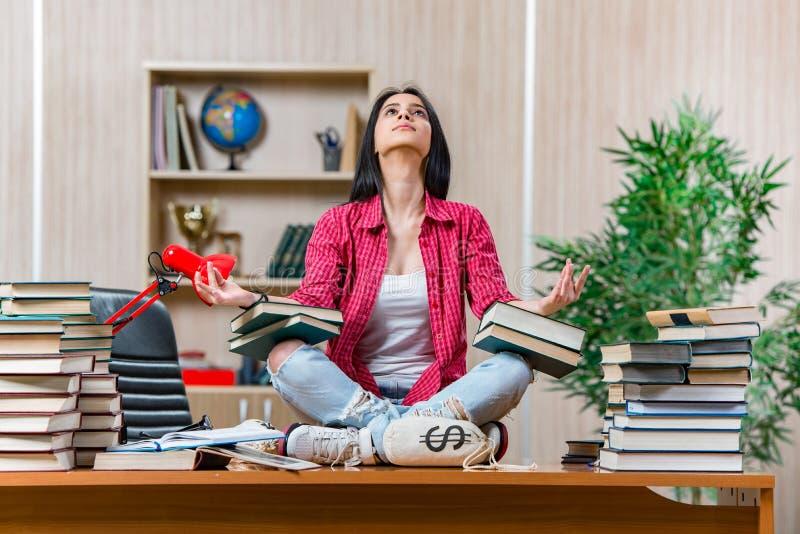 De jonge vrouwelijke student die voor de examens van de universiteitsschool voorbereidingen treffen royalty-vrije stock afbeeldingen