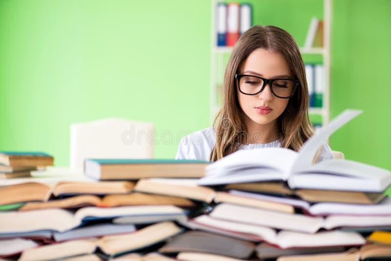 De jonge vrouwelijke student die voor examens met vele boeken voorbereidingen treffen stock foto's